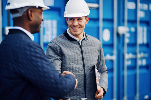 Smiling engineers standing in a shipping yard shaking hands together stock photo