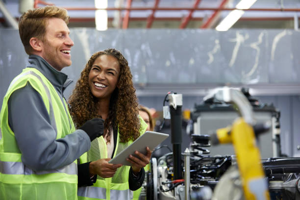 Smiling engineers standing with digital tablet Happy mechanical engineers holding digital tablet by car chassis at factory. Smiling colleagues are standing by car part at automobile industry. They are wearing reflective clothing. mechanical engineering stock pictures, royalty-free photos & images