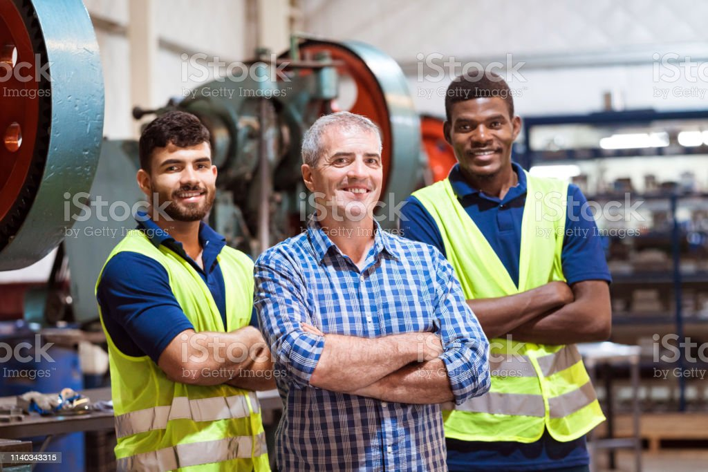 Smiling engineers with arms crossed in factory Smiling male engineers with arms crossed in manufacturing industry. Expertise are standing in company. They are with confident look on their faces. 20-24 Years Stock Photo
