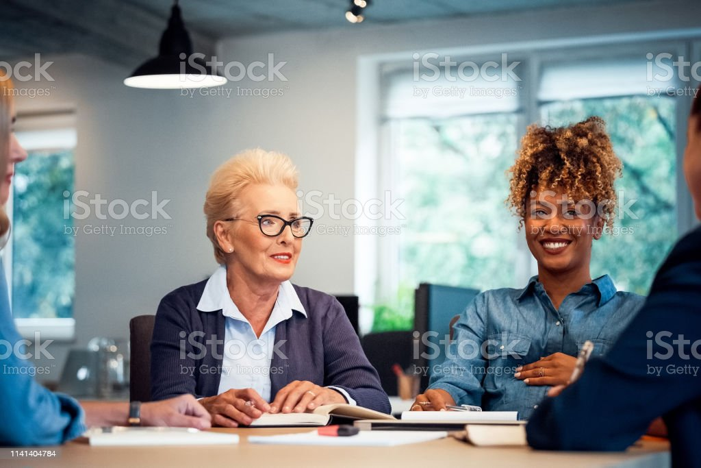 Smiling entrepreneurs discussing new business plan Smiling entrepreneurs discussing new business plans. Confident colleagues are working together at desk in office. They are cooperative to each other. 35-39 Years Stock Photo