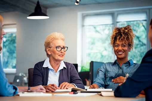 Smiling Entrepreneurs Discussing New Business Plan Stock Photo - Download Image Now
