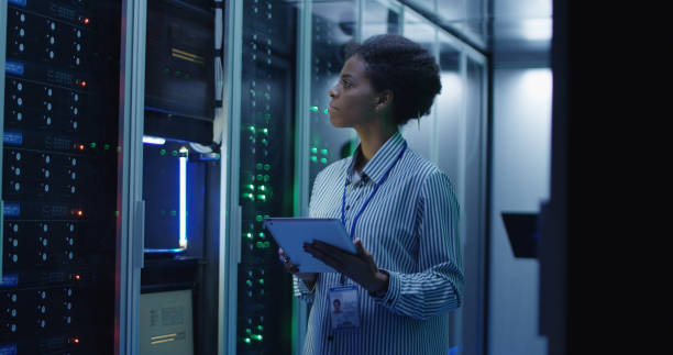 Smiling ethnic woman in data center Portrait of African American woman working as IT engineer and standing among server racks in data center room technician stock pictures, royalty-free photos & images