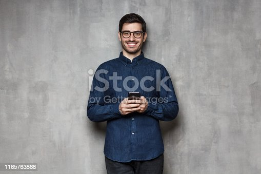 825083556istockphoto Smiling european man in denim shirt and trendy glasses standing against gray textured wall, holding his phone with both hands 1165763868