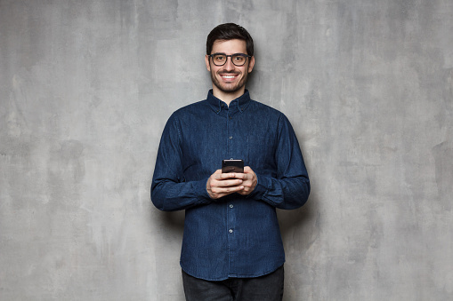 825083556 istock photo Smiling european man in denim shirt and trendy glasses standing against gray textured wall, holding his phone with both hands 1165763868
