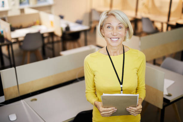Smiling excited confident lady with badge hanging on neck standing in open space office and looking at camera stock photo