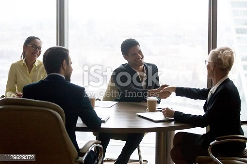 istock Smiling executive businesswoman handshaking african businessman at group meeting 1129629372