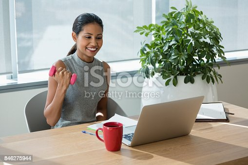 istock Smiling executive exercising with dumbbells while working laptop 846275944