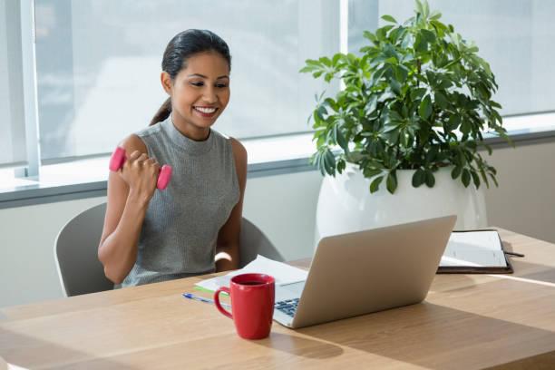 lächelnd, executive training mit hanteln beim laptop arbeiten - trainingstagebuch stock-fotos und bilder
