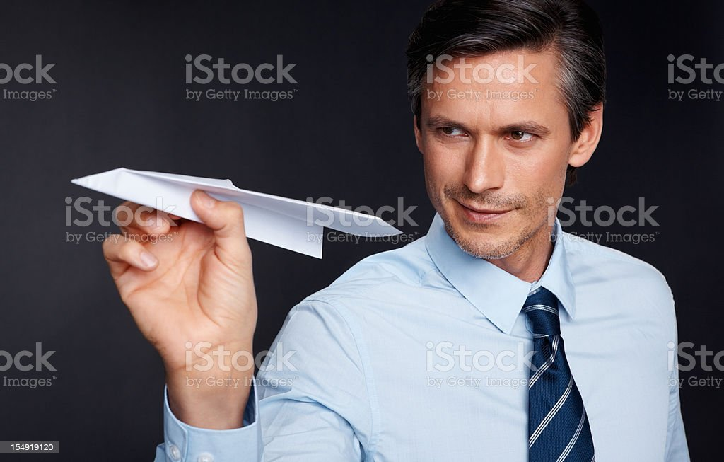 Smiling executive holding paper airplane royalty-free stock photo