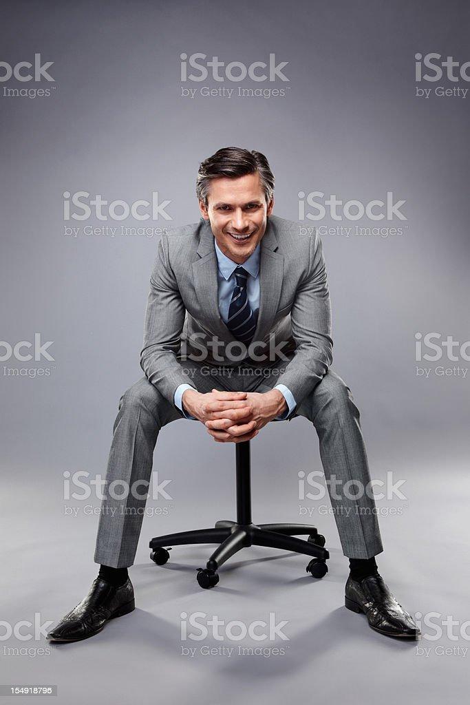 Smiling executive sitting on a stool stock photo