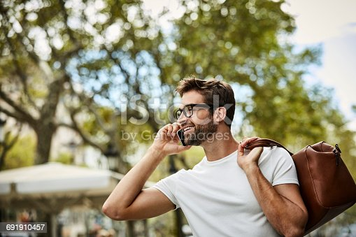 istock Smiling executive talking on phone and holding bag 691910457