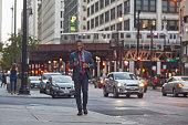 Smiling businessman using smart phone on city street. Confident executive is walking against buildings and cars. Male professional is in suit.