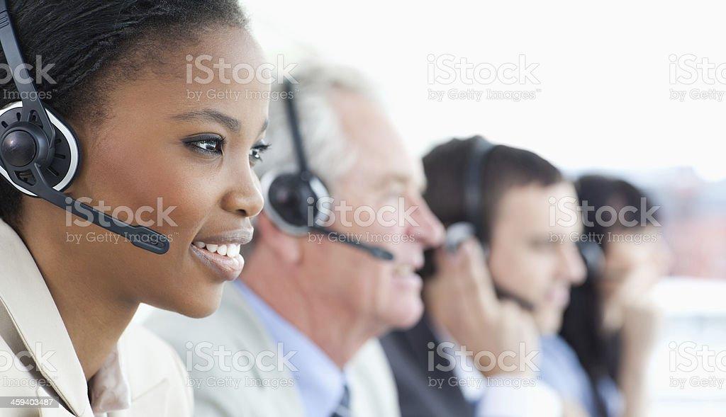 Smiling executive wearing a headset to communicate accompanied b stock photo