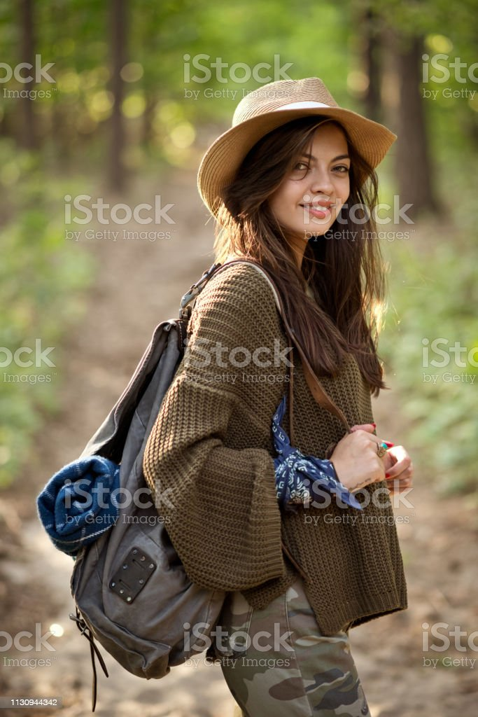 Smiling explorer standing with backpack in forest Portrait of smiling young woman in forest. Side view of female explorer is with backpack. Hiker is wearing hat. 25-29 Years Stock Photo