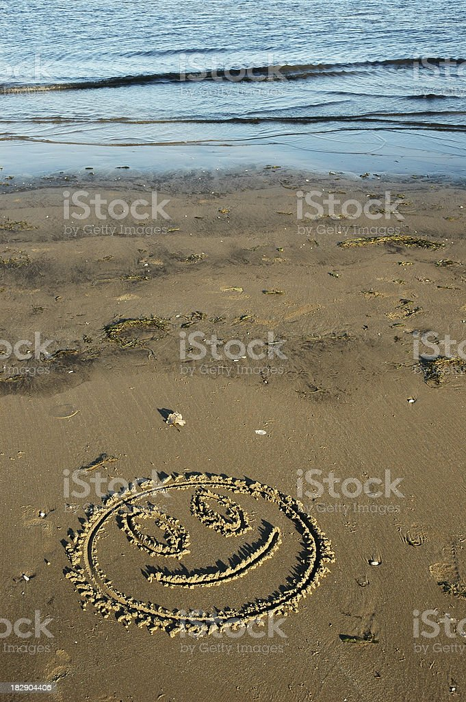 Smiling Face in Sand stock photo