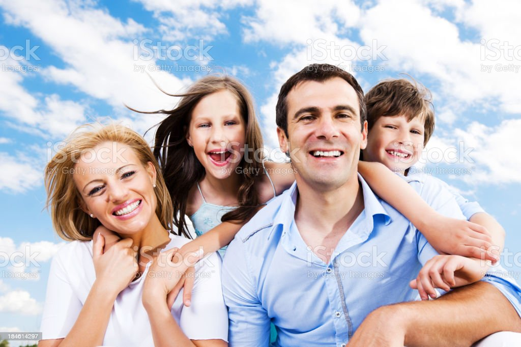 Smiling family against the sky and clouds. royalty-free stock photo