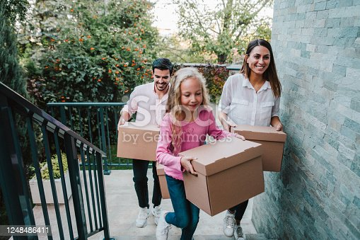 Portrait of happy family with one child moving to new house with cardboard boxes. A young family move into their new home. Smiling family carrying boxes into new home on moving day. Family entering in their new house.