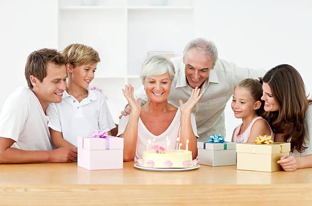 lächelnden familie feiert geburtstag - geburtstagsgeschenk für papa stock-fotos und bilder