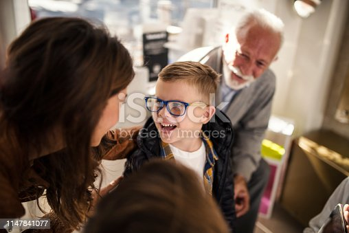 Smiling family choosing the most suitable eyeglasses at optician store.