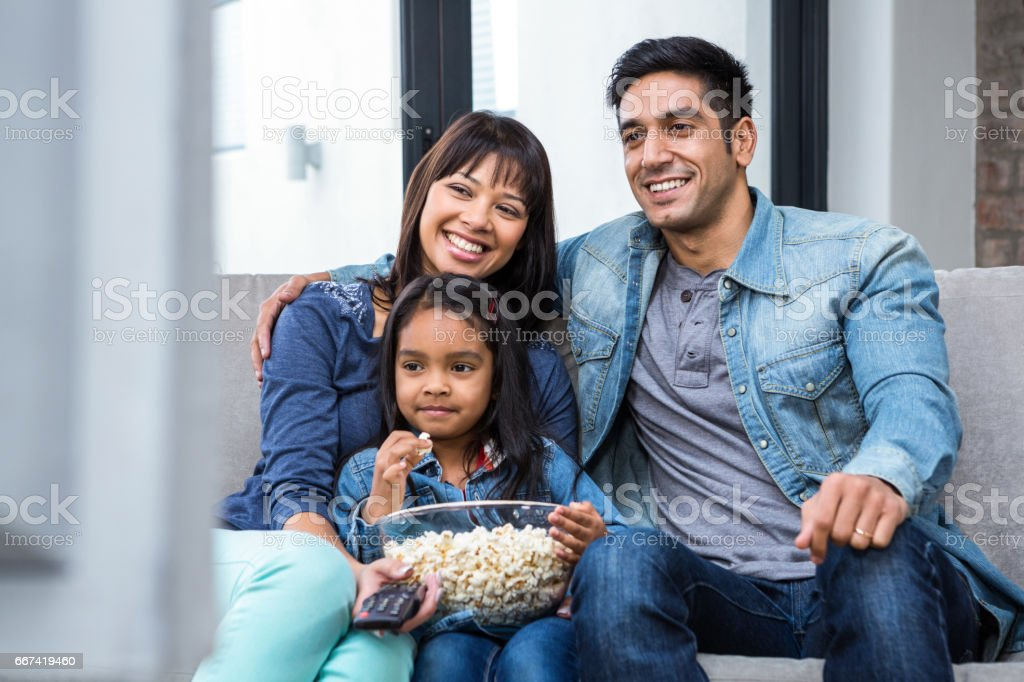 Smiling family eating popcorn while watching tv stock photo