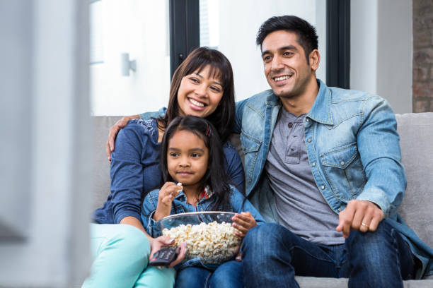 smiling family eating popcorn while watching tv - family watching tv stock photos and pictures