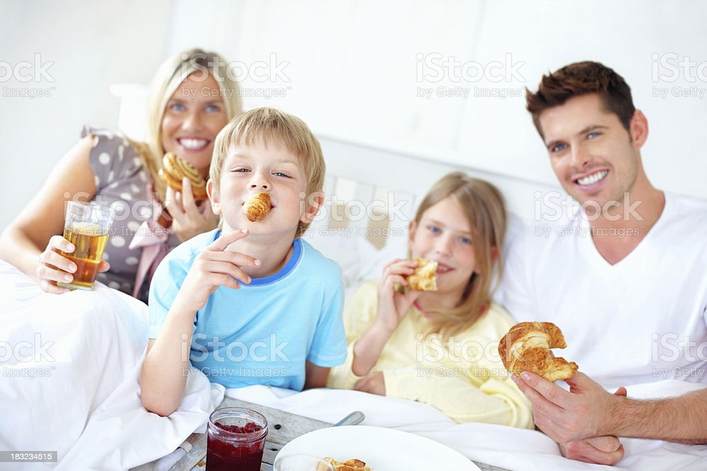 Smiling family having breakfast in bed royalty-free stock photo