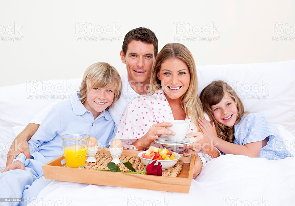 Smiling family having breakfast sitting on bed royalty-free stock photo