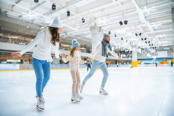 smiling family holding hands while skating together on ice rink smiling family holding hands while skating together on ice rink ice skating stock pictures, royalty-free photos & images