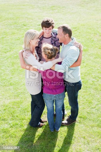 585604690 istock photo Smiling family hugging in a circle on grass 103332387