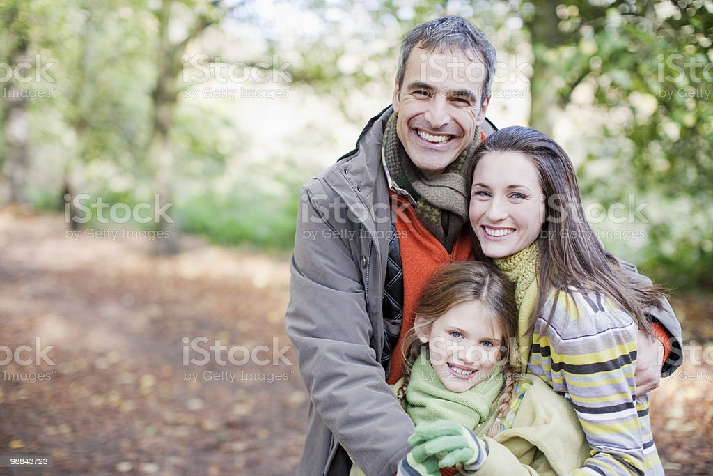 Smiling family hugging outdoors royalty free stockfoto