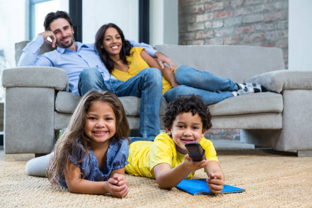 Smiling family in living room looking tv stock photo