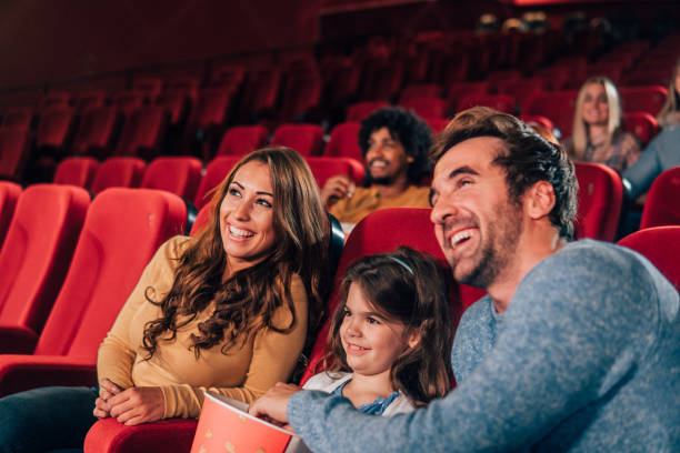 smiling family in the cinema - movie theater stock pictures, royalty-free photos & images