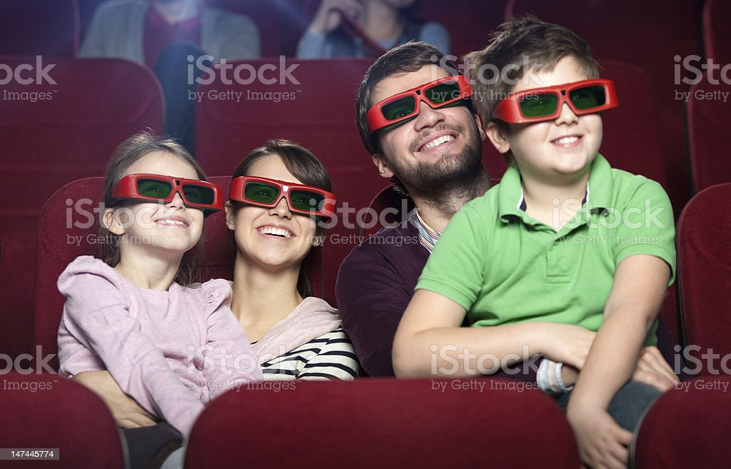 Smiling family in the movie theater stock photo
