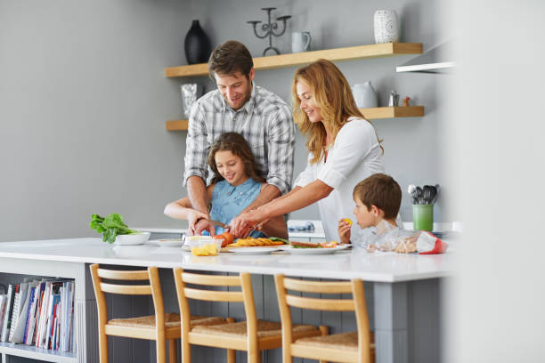 Smiling family making lunch together in their kitchen stock photo