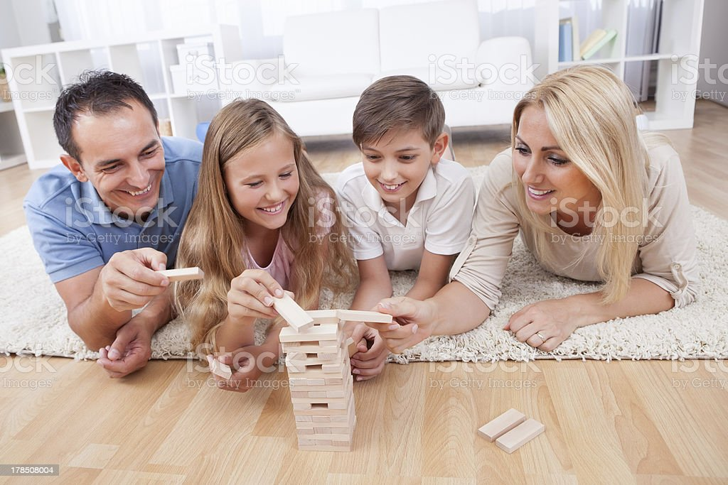 Smiling family of four lying down playing with wood blocks stock photo