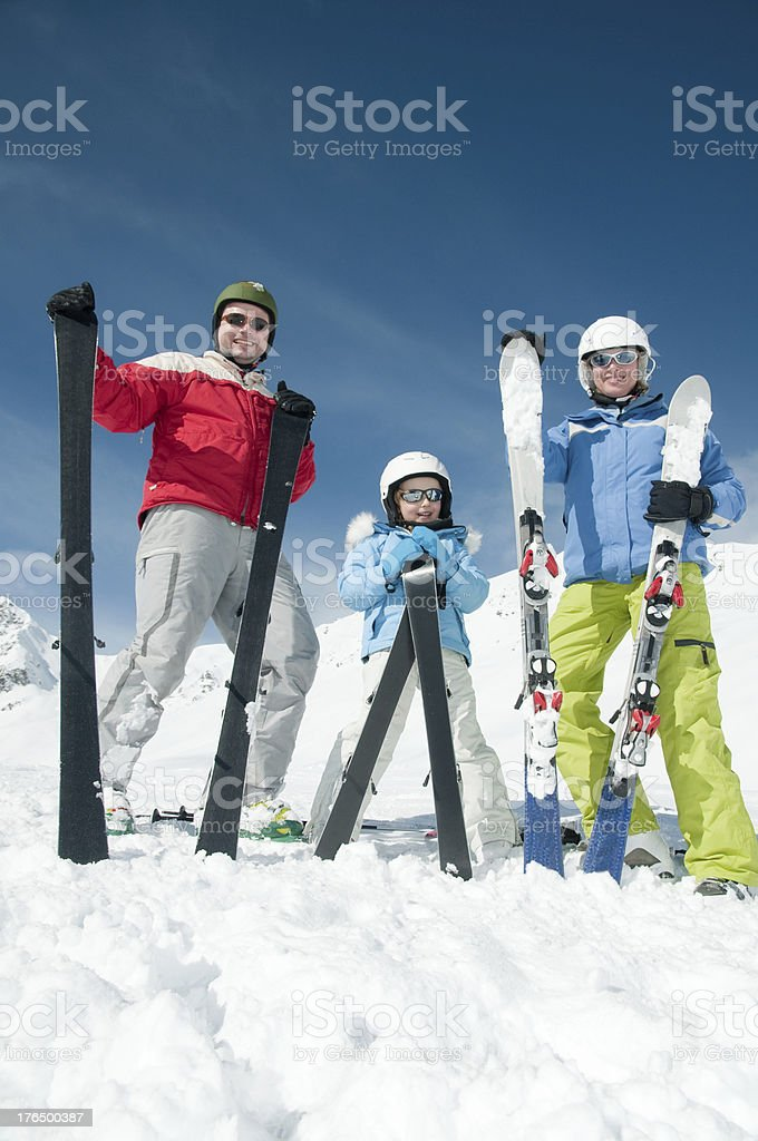 Smiling family of three skiing on a nice day royalty-free stock photo