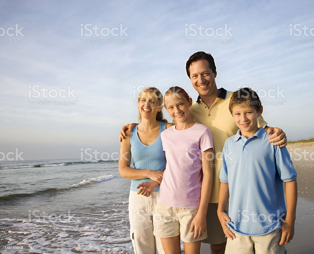 Smiling family on beach. stock photo