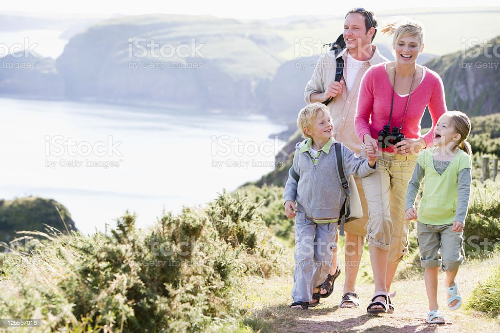 Smiling family on cliff side path royalty-free stock photo