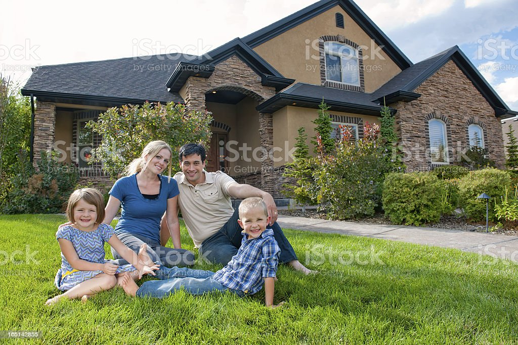 Smiling family on front lawn of a house stock photo