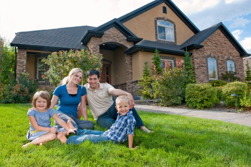 Smiling Family On Front Lawn Of A House Stock Photo - Download Image Now