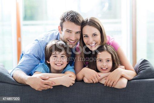 istock Smiling family on sofa 474857020