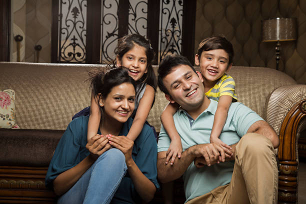 Smiling family on sofa - Stock image Family, Living Room, Home Interior, Daughter, Offspring indian family stock pictures, royalty-free photos & images