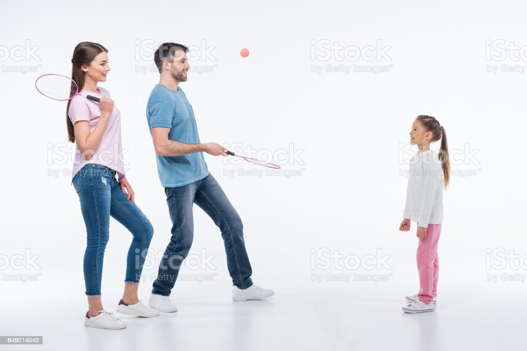 smiling family playing badminton with rackets and shuttlecock on white - Photo