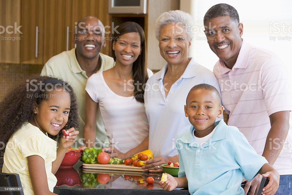 A smiling family preparing a healthy meal together royalty-free stock photo