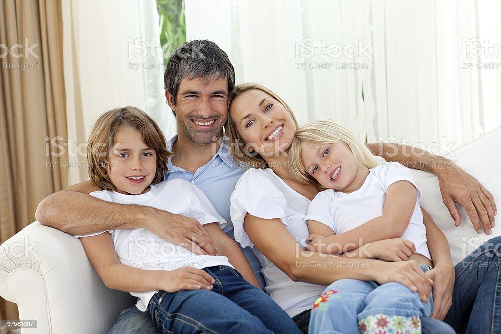 Souriant famille détente sur le canapé-lit photo libre de droits