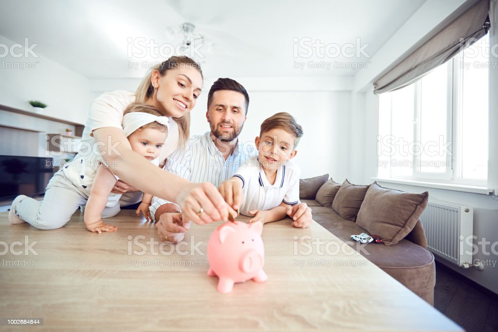 A smiling family saves money with a piggy bank stock photo
