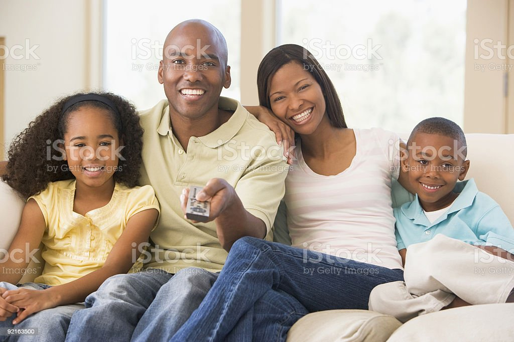 Smiling family sitting holding remote control royalty-free stock photo
