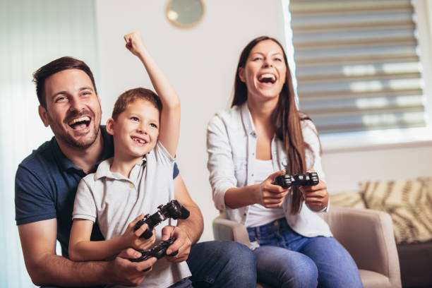 smiling family sitting on the couch together playing video games - gaming zdjęcia i obrazy z banku zdjęć