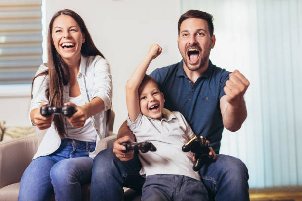 Smiling family sitting on the couch together playing video games stock photo