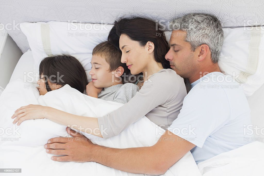 Smiling family sleeping together in bed royalty-free stock photo